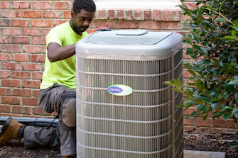 HVAC service professional working on an air conditioning unit in Raleigh